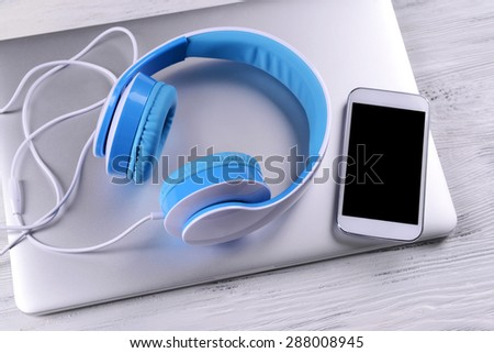 Headphones with laptop on table close up - stock photo