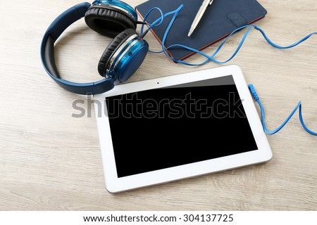 Headphones with tablet and notebook on wooden table close up - stock photo