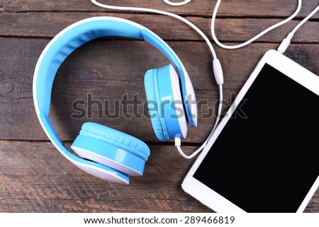 Headphones with tablet on wooden background