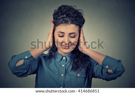 Headshot beautiful young woman covering both ears with her hands isolated on gray wall background  - stock photo