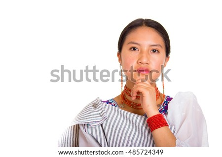 Headshot beautiful young woman wearing traditional andean shawl and red necklace, posing for camera using hands touching head interacting, white studio background
