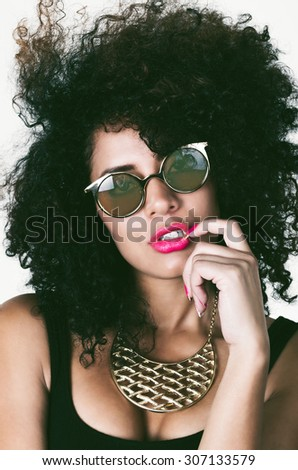 Headshot brunette model with afro like hair, sunglasses, pink lipstick and large golden necklace posing for camera touching lips using left hand. - stock photo