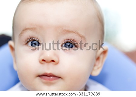 Headshot of a baby with blue eyes looking to the camera  - stock photo