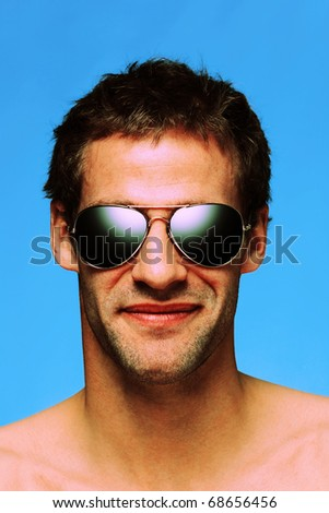 Headshot of a caucasian man in his late twenties with designer stubble wearing aviator sunglasses taken against a plain blue background, cross processed color effect. - stock photo