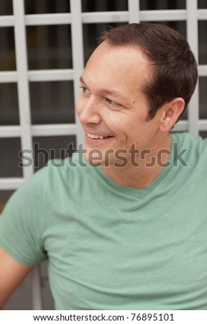Headshot of a handsome man smiling and glancing away - stock photo