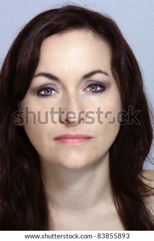 Headshot of a lovely brunette with a neutral facial expression.