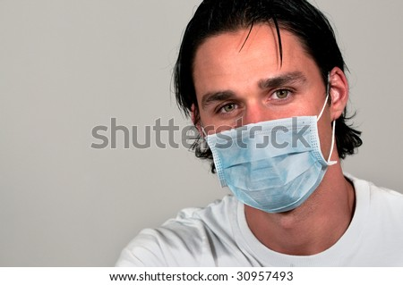 Headshot of a man wearing a blue medical mask on grey background. - stock photo