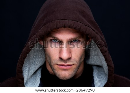 Headshot of a man wearing a brown hooded top with an intense stare - stock photo