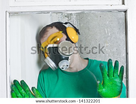 Headshot of a worker in protective workwear located behind the transparent glass and wood frame - stock photo