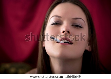 Headshot of a young beautiful woman with a cigarette in her mouth - stock photo
