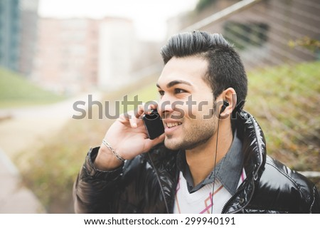 Headshot of a young handsome indian contemporary businessman talking smartphone with earphone already on - business, finance, technology concept
