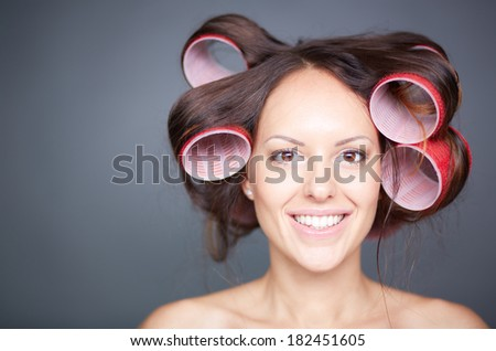 Headshot of a young woman with hair curlers over grey background  - stock photo