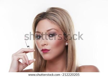 headshot of beautiful female model holding a syringe  - stock photo