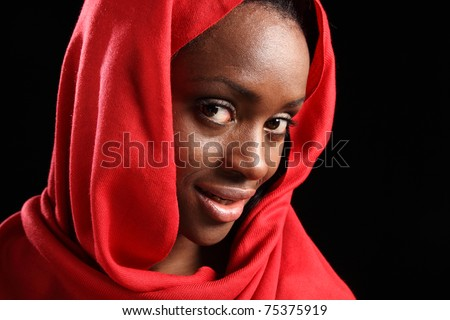 Headshot of beautiful young black muslim girl wearing red hijab, with a happy smile on her face. - stock photo