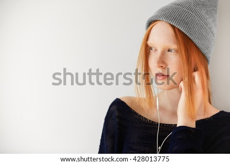 Headshot of Caucasian female teenager listening to music on electronic device with headphones. Pretty student girl wearing earphones listening to audiobook while preparing for exams at university  - stock photo