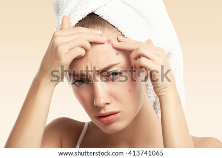 Headshot of displeased young blond woman with towel on her head, looking with painful face at the camera while squeezing pimple on her forehead. Portrait of Caucasian girl against blue wall background - stock photo