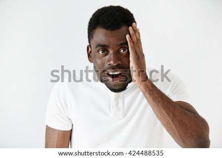 Headshot of handsome surprised African American young man looking at the camera, astonished with big sale prices against white background. Human face expression, emotion, feeling, reaction, attitude - stock photo