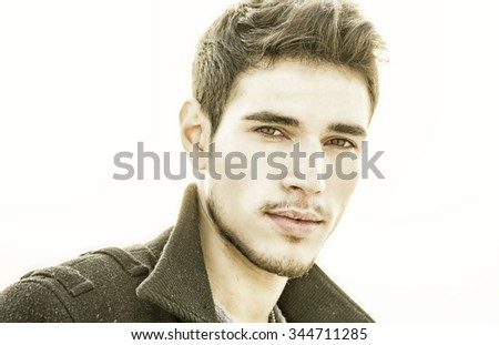 Headshot of handsome young man outdoor, lit by sunset light, looking at camera - stock photo