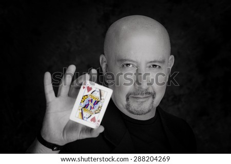 Headshot of magician man posing for camera showing a queen of hearts black and white editiom - stock photo
