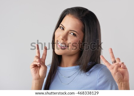 Headshot of pretty woman making hand gesture peace sign, like a tourist posing