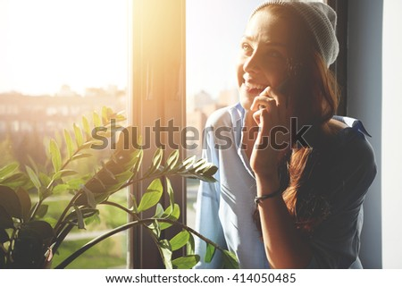 Headshot of redhead Caucasian student girl talking on smart phone to friends discussing plans on weekend. Young beautiful woman laughing while chatting on cell phone with her boyfriend. Flare sun   - stock photo