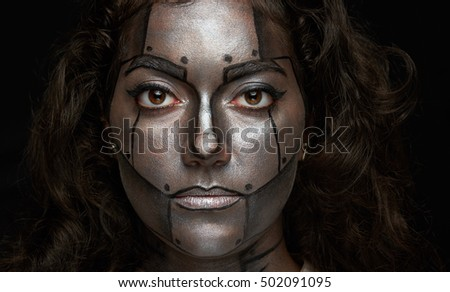 headshot of women with metal paint body art isolated on black