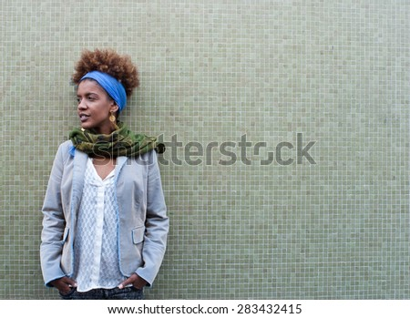 Headshot of young afro american curly woman in front of tiled background - free text space - stock photo
