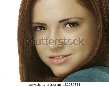 Headshot portrait of an attractive young woman with red hair and a green outfit.  - stock photo