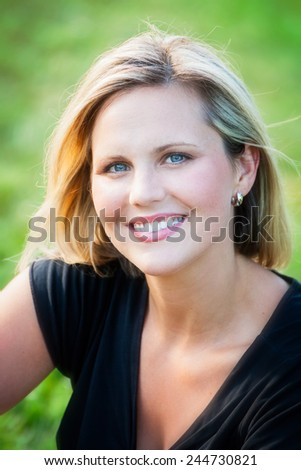 Headshot portrait of an early 30s casual happy beautiful blond woman at the park on a sunny summer day - stock photo