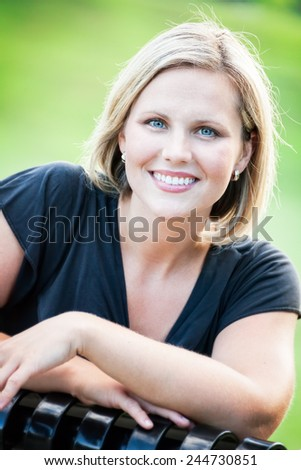 Headshot portrait of an early 30s casual happy beautiful blond woman sitting on a park bench at the park on a sunny summer day