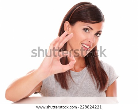 Headshot portrait of attractive young girl with positive gesture looking at camera on isolated studio - stock photo