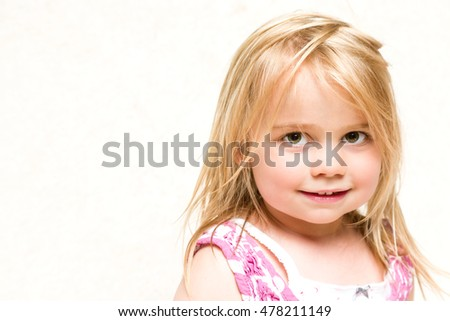 Headshot Portrait of Beautiful Smiling Toddler Girl with Tousled Blonde Hair Copy Space