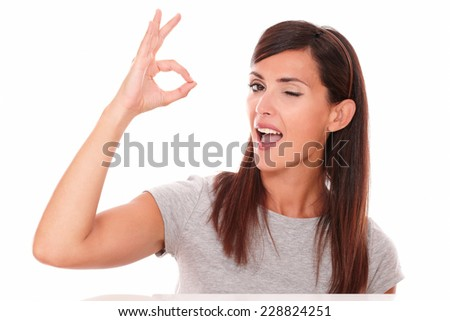 Headshot portrait of cheerful adult lady with ok sign winking and looking at you on isolated studio - stock photo