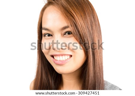 Headshot portrait of good looking, gorgeous, charming Asian girl with light brown hair smiling positively showing genuine, real friendly and approachable nature. Thai national of Chinese origin