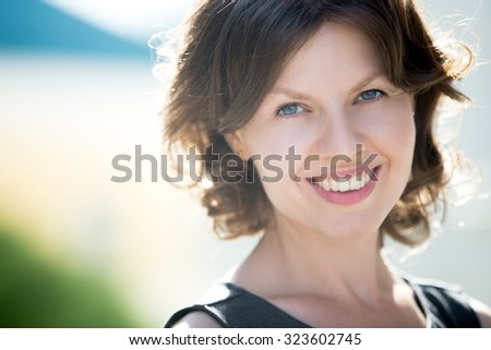 Headshot portrait of happy beautiful caucasian woman on the street in summer, friendly smiling, looking at camera with cheerful confident expression - stock photo
