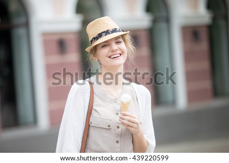 Headshot portrait of laughing beautiful caucasian woman holding one ice cream wearing casual clothing and straw hat. Young person eating ice-cream cone on summer street and looking at camera - stock photo