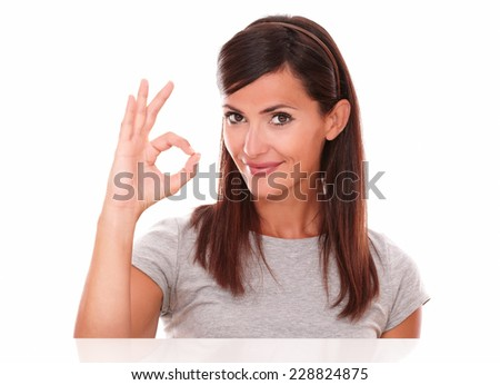 Headshot portrait of positive happy brunette with ok sign looking at you on isolated studio - stock photo