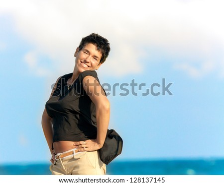 Headshot portrait of smiling woman on clear blue sky