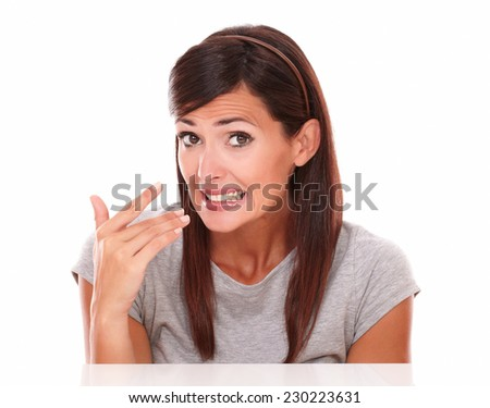 Headshot portrait of surprised hispanic woman with mistake gesture looking at camera on isolated white background