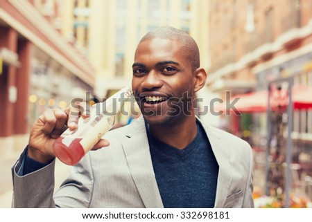 Headshot portrait of young smiling man drinking soda from glass bottle isolated on outside outdoors urban street background. - stock photo