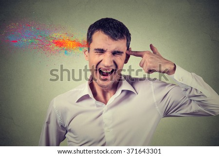 Headshot portrait young man committing suicide with finger gun gesture, explosion of colors isolated on grey wall background. Human emotions face expressions - stock photo