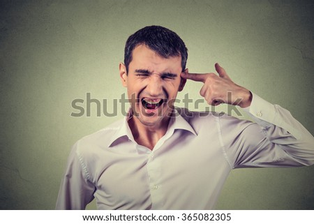 Headshot portrait young stressed man committing suicide with finger gun gesture isolated on grey wall background. Human emotion face expression. Overworked overwhelmed young man. Too many things to do - stock photo