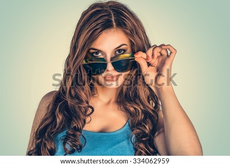 Headshot serious angry bitchy woman wife holding sunglasses down skeptically looking at you isolated green yellow wall background, blue shirt. Human face expression body language, attitude, perception - stock photo