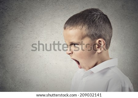 Headshot, side view Portrait Angry Child Screaming isolated grey wall background. Negative Human face Expressions, Emotions, Reaction, Perception. Conflict, confrontation concept - stock photo