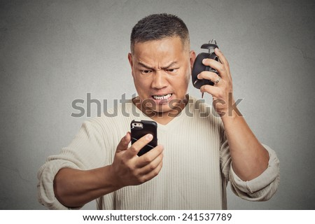 Headshot unhappy angry middle aged man with alarm clock looking at smart phone with frustrated face expression late for meeting isolated grey background. Human expression emotion feeling reaction - stock photo