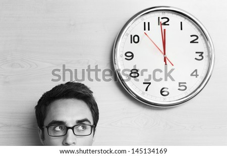 Headshot young businessman wearing spectacles looking at clock on wall in office - stock photo