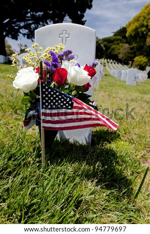 Headstone, American Flag, and floral display at an American National Military Cemetery