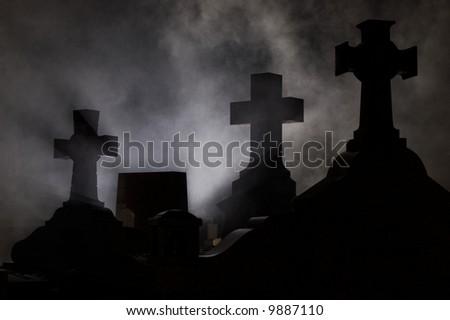 Headstone cross in Graveyard at night. - stock photo
