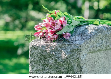Headstone in cemetery with flowers for concept of death and loss - stock photo