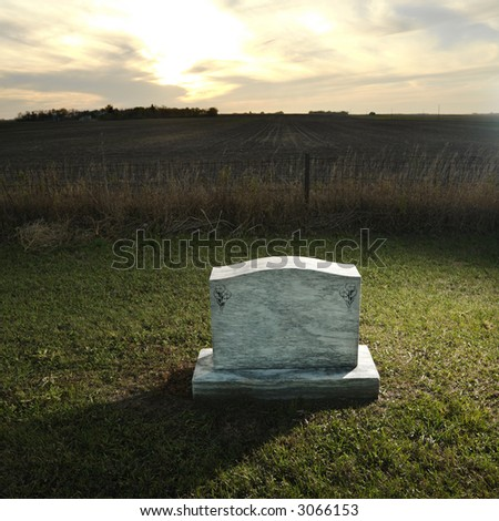 Headstone marking grave in rural countryside at sunset. - stock photo